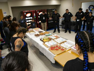 Valerie Zamarripa with family members prays with the Dallas Police Southwest Patrol division before serving them breakfast on Friday, July 2, 2021, in Dallas. Valerie Zamarripa's son, Patrick Zamarripa, was one of the five officers who were killed when a gunman ambushed a night of protests in downtown Dallas on July 7, 2016. (Juan Figueroa/The Dallas Morning News)