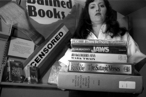 """Melissa King Odle holds a stack of books as part of a the """"Banned Books"""" display in the Dallas Public Library in 1993."""