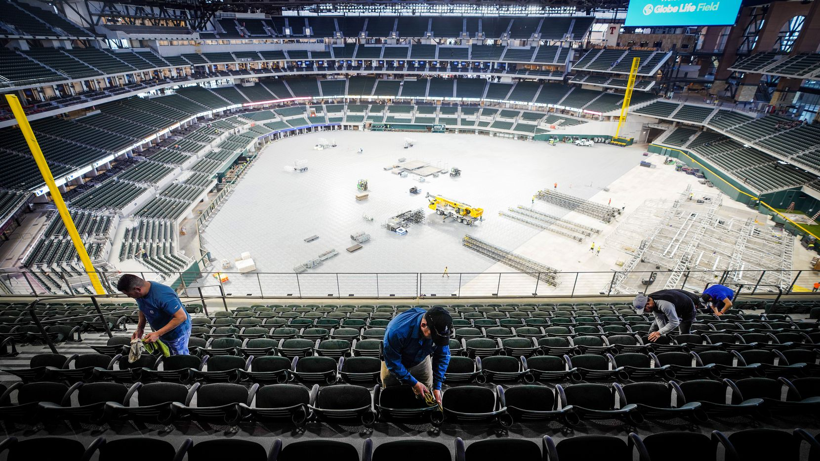 Crews clean seats on the upper concourse at the Texas Rangers' new Globe Life Field as preparations for an upcoming concert are made on the stadium floor on Wednesday, March 11, 2020, in Arlington.