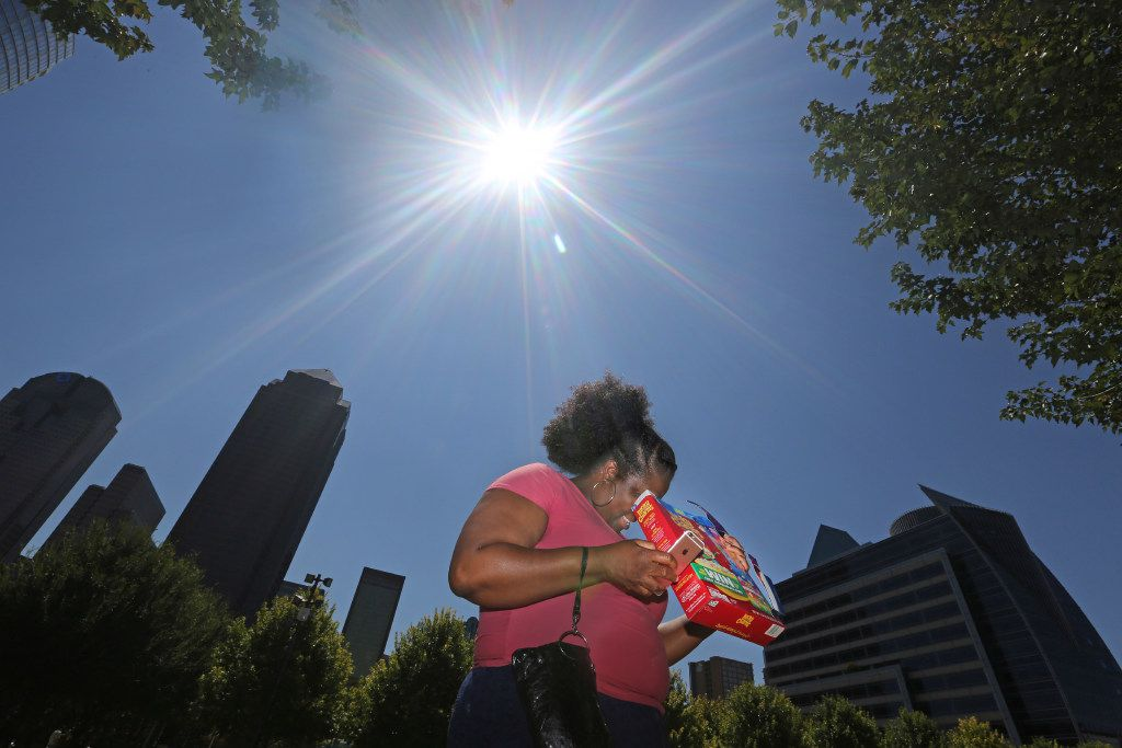 Tiffany Francis used a Lucky Charms cereal box to view the partial solar eclipse at Klyde Warren Park in Dallas on Monday.