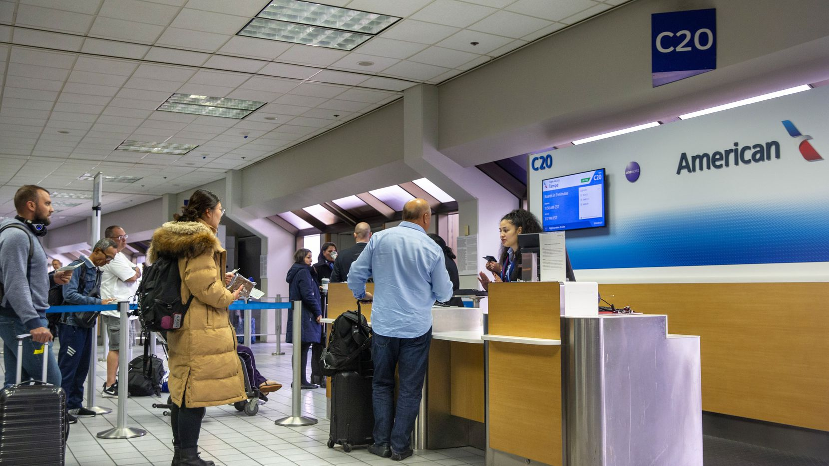 Passengers wait at an American Airlines ticket counter at DFW International Airport in Irving on Nov. 22, 2019. American Airlines is bumping passengers from overbooked flights at an industry-leading rate.