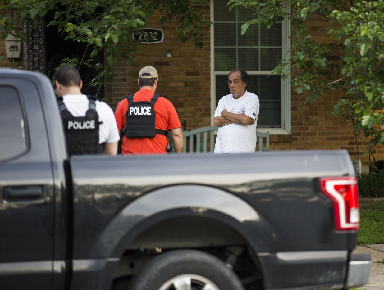 Police officers stand outside a home belonging to relatives of a man who shot two officers outside a Home Depot on April 24, 2018 on Hedgerow Drive in Dallas.