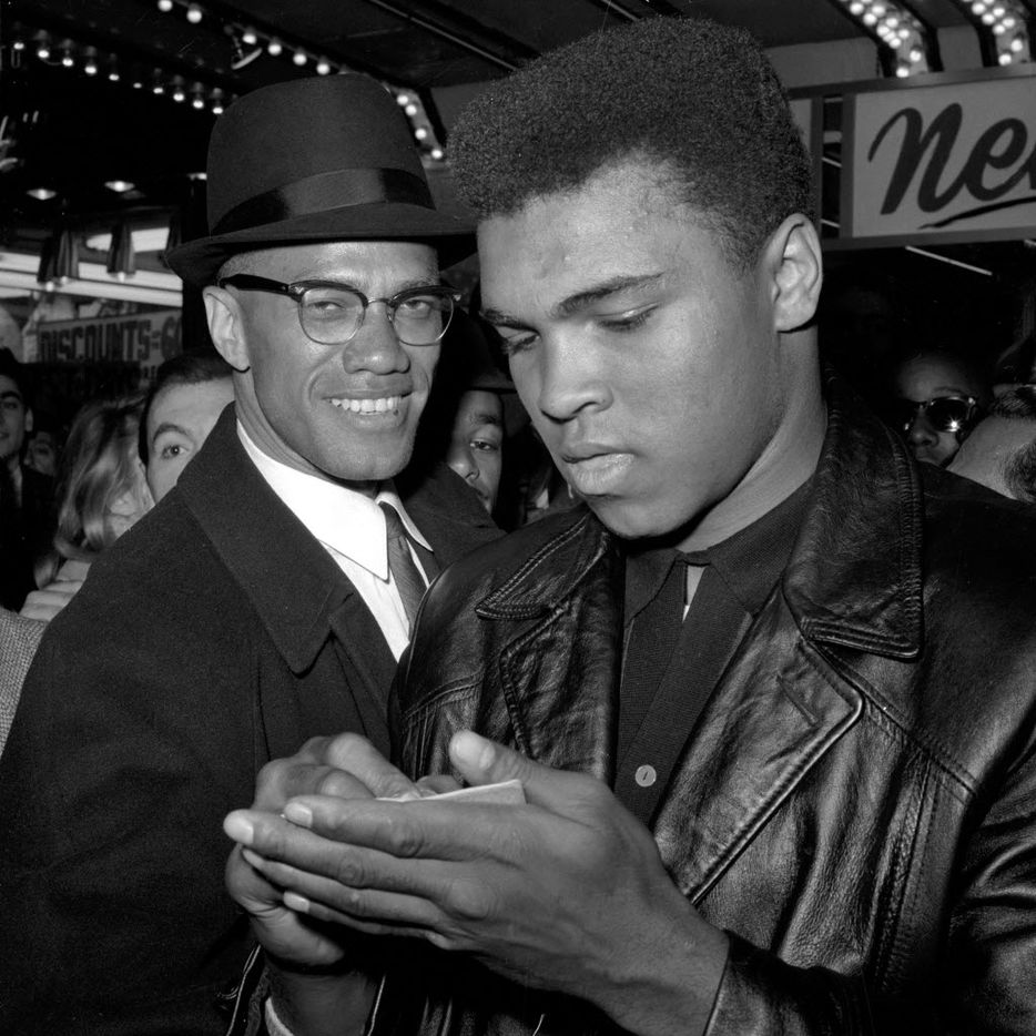 ADVANCE FOR USE SUNDAY, FEB. 23, 2014 AND THEREAFTER - FILE - In this March 1, 1964 file photo, Muhammad Ali, world heavyweight boxing champion, right, stands with Malcolm X outside the Trans-Lux Newsreel Theater on Broadway at 49th Street in New York. They had just watched a screening of films on Ali's Feb. 25, 1964 title fight with Sonny Liston in Miami Beach. (AP Photo)
