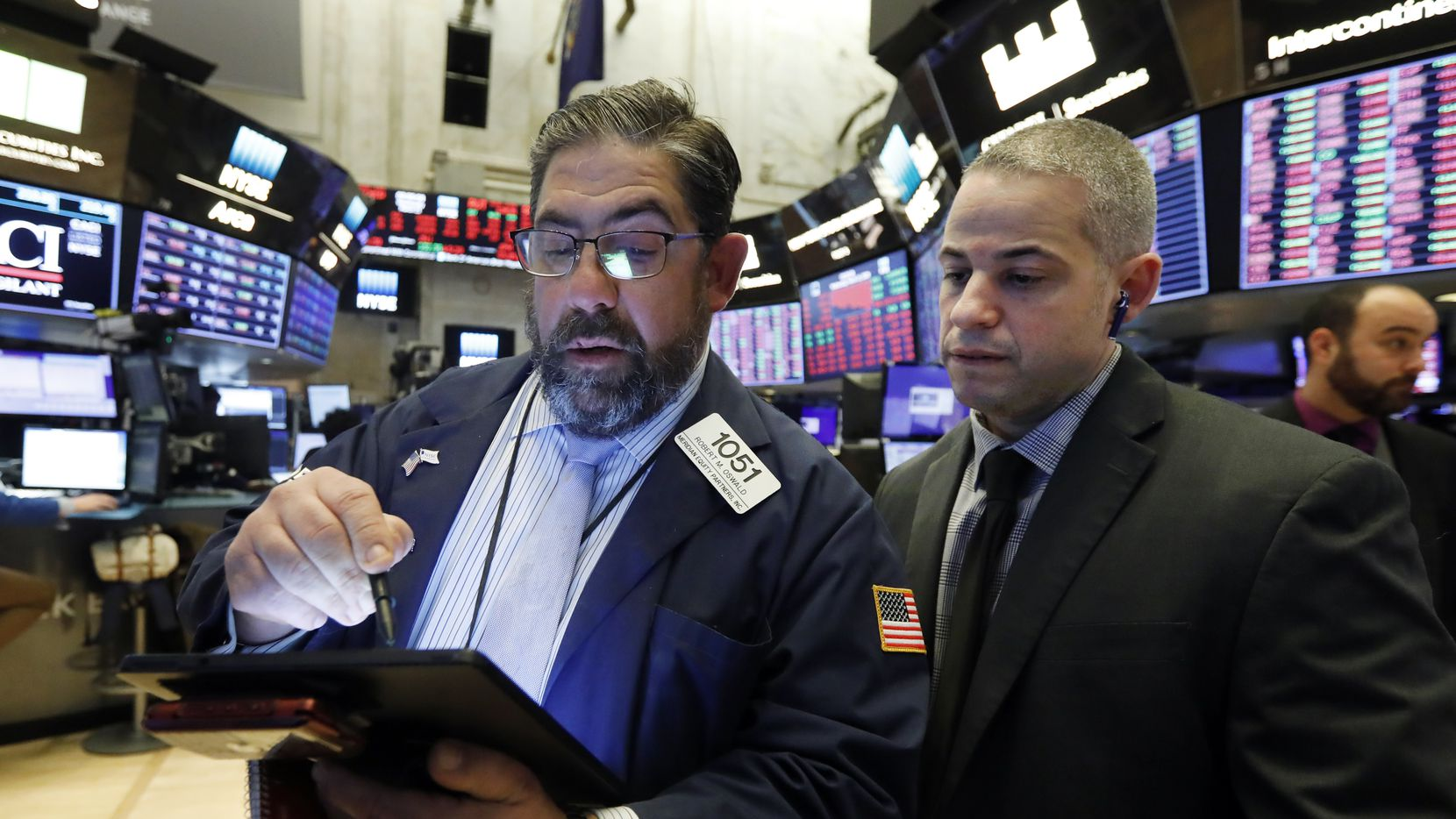 Director of trading floor Ooperations Fernando Munoz, right, works with trader Robert Oswald on the floor of the New York Stock Exchange on Wednesday.