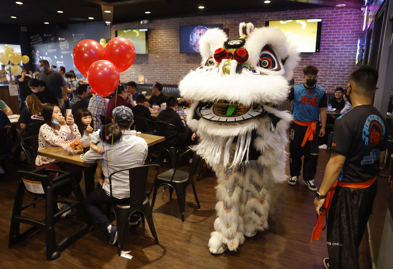 Customers watch as costumed entertainers make their way through the dining area of BB.Q Chicken during a grand opening event.