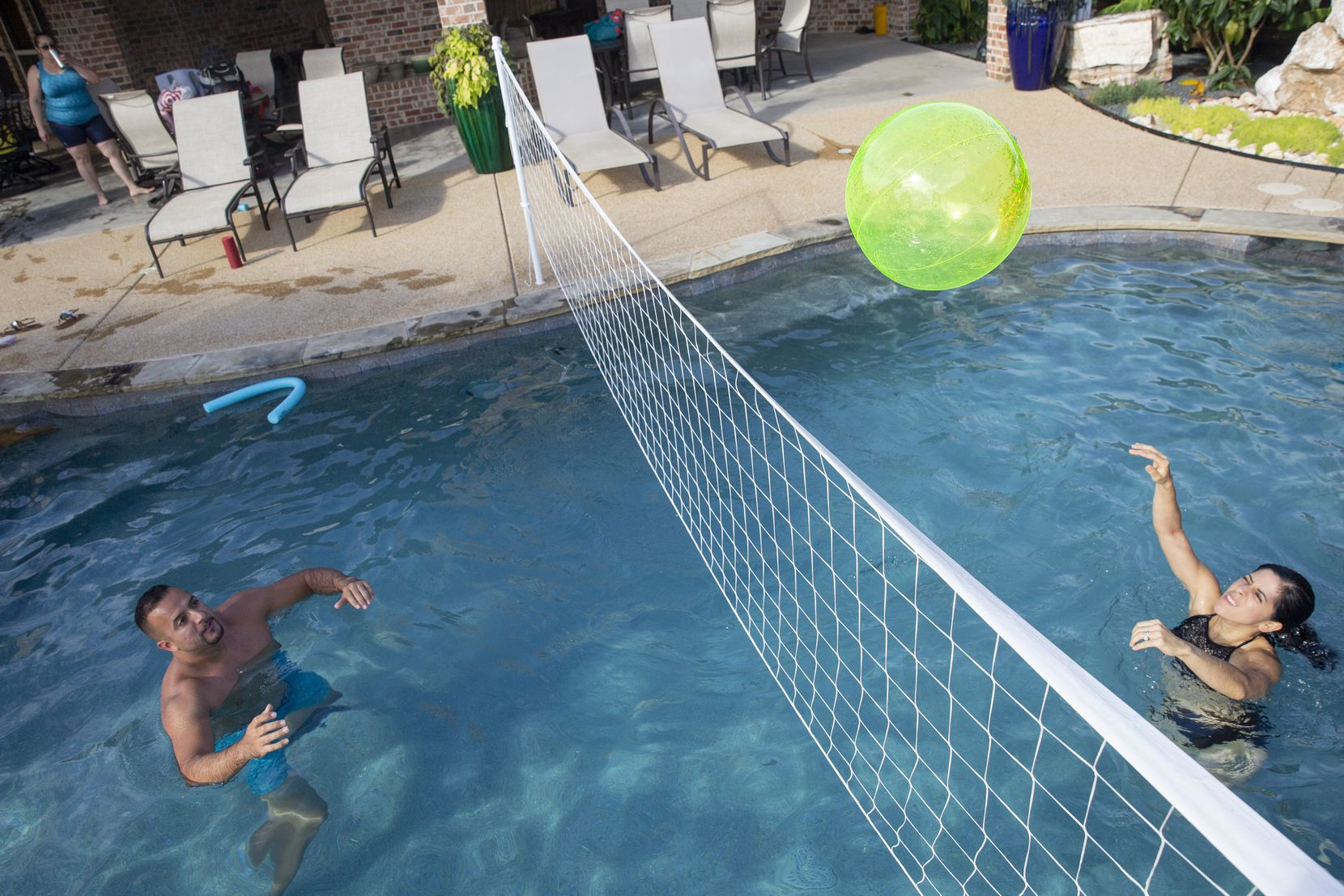 Tony Banda (left) and sister Imelda Mendoza pass the ball at a pool they rented using the Swimply app on July 26 in Waxahachie. Their sister Adriana Banda reserved the pool for the family.