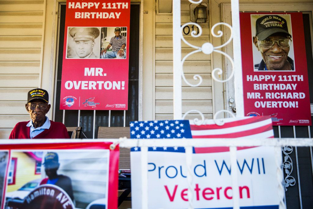 Richard Overton, 112, smoked a cigar on his front porch on Richard Overton Avenue in Austin on May 25, 2017, among signs displayed to celebrate his birthday. Overton is known for smoking cigars and drinking whiskey on his front porch. He is the oldest living U.S. war veteran.
