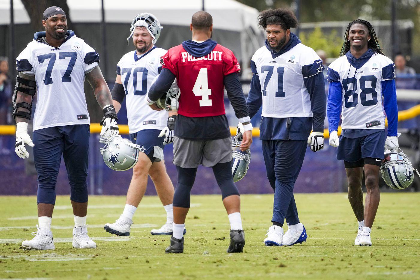 Dallas Cowboys quarterback Dak Prescott (4) talks with tackle Tyron Smith (77), guard Zack Martin (70), tackle La'el Collins (71) and wide receiver CeeDee Lamb (88) between drills during a practice at training camp on Saturday, July 24, 2021, in Oxnard, Calif.