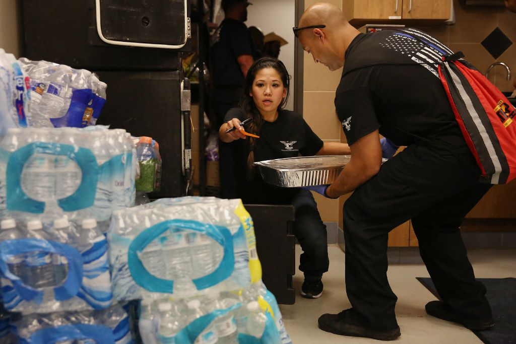 Jennifer Do directs Houston police Officer Mike Enriquez as she helps to manage the kitchen at the Houston Police Officers' Union in Houston on Wednesday. Do and her friend Dory Fung have been managed the food for the union as donation have streamed into the kitchen to feed Houston officers.
