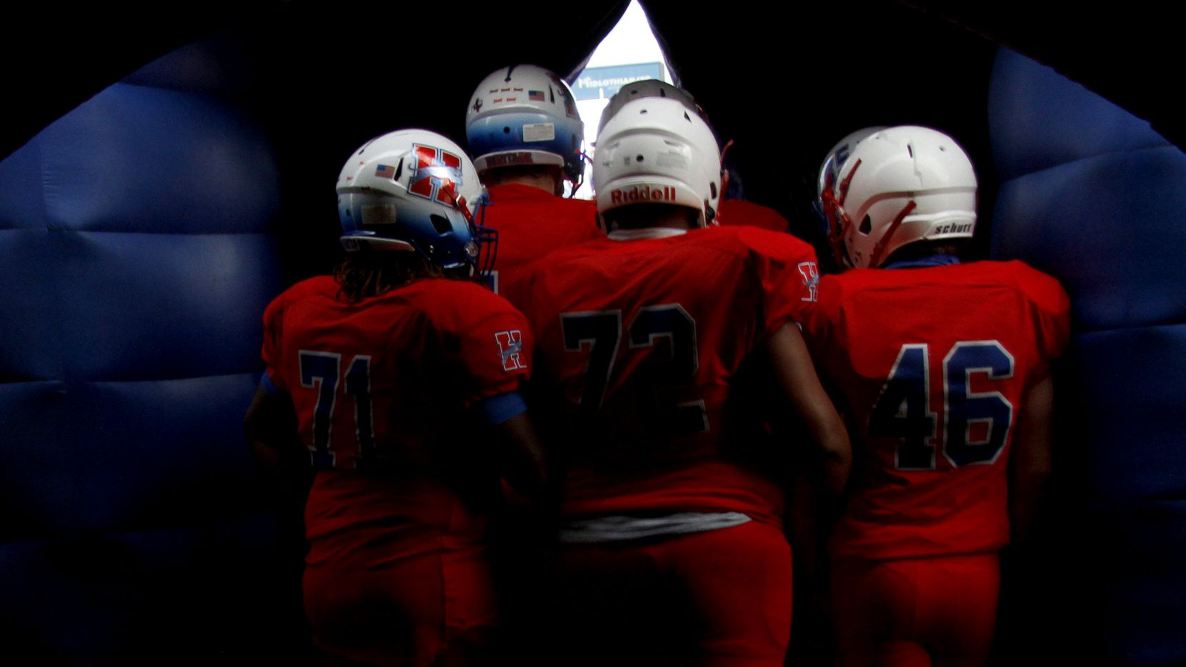 Midlothian Heritage players huddle and peek through an opening of their team inflatable prior to team announcements before the kickoff of their game against Lindale. The two teams played their Class 4A football game at Midlothian ISD Multipurpose Stadium in Midlothian on September 4, 2020.