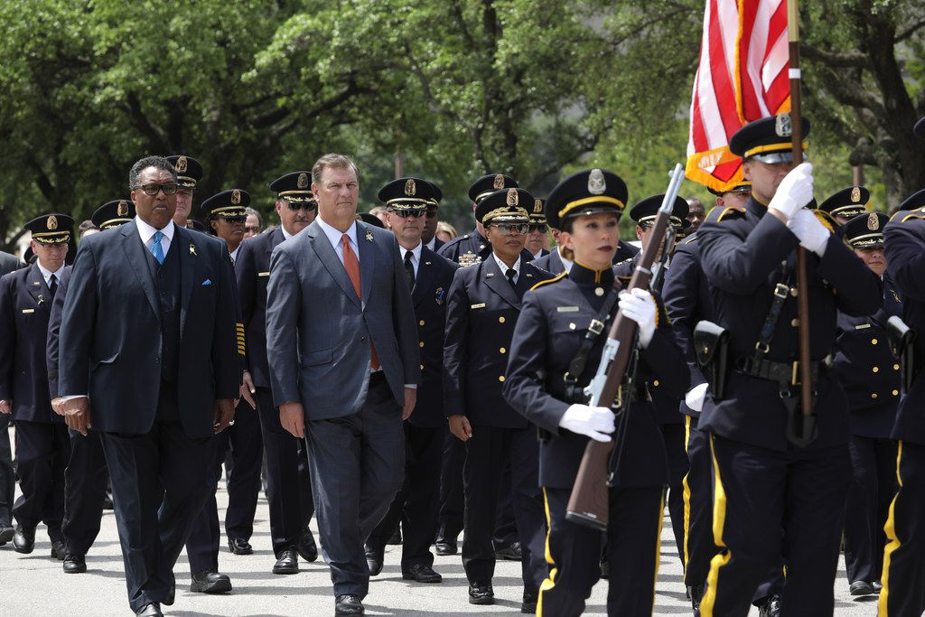 Dwaine Caraway (left) and Mike Rawlings join police and community members in a march Wednesday marking Police Memorial Day. (Jason Janik/Special Contributor)