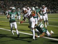 Rockwall Heath player Jay Fair (1) scores a touchdown in front of Southlake's Mason Grawe (27) and Benecio Porras (32) during their high school football game in Southlake, Texas, on Oct. 2, 2020.