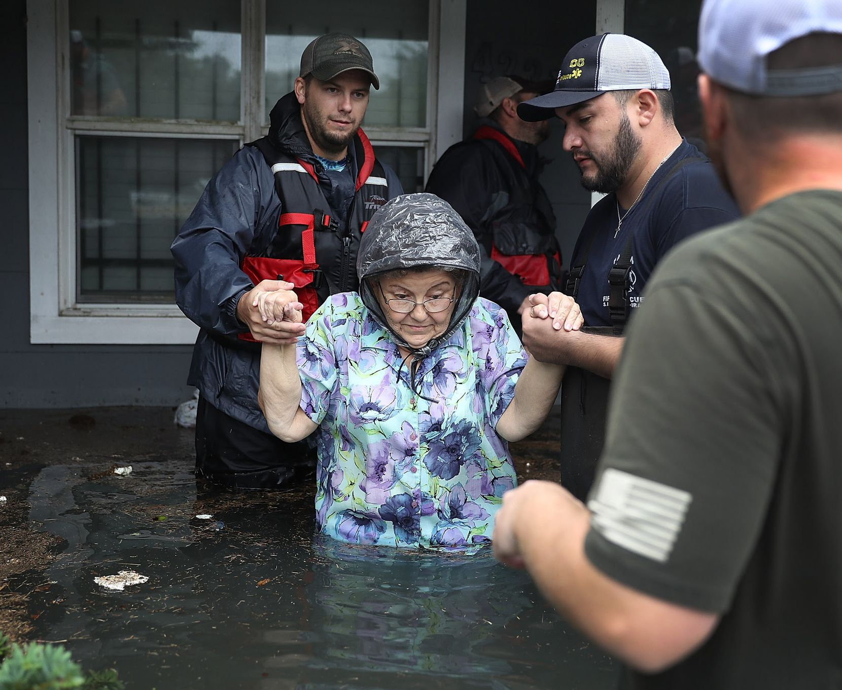 Volunteer rescuer workers help a woman from her home that was inundated with the flooding of Hurricane Harvey on August 30, 2017 in Port Arthur, Texas. Harvey, which made landfall north of Corpus Christi late Friday evening, is expected to dump upwards to 40 inches of rain in Texas over the next couple of days.