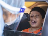 Elizabeth Osborn, medical assistant at WellHealth, swabs Josiah Soto's mouth for COVID-19 at Sharing Life Community Outreach, a nonprofit that provides food and other resources, in Mesquite. The nonprofit has partnered with GoGetTested to offer free testing.