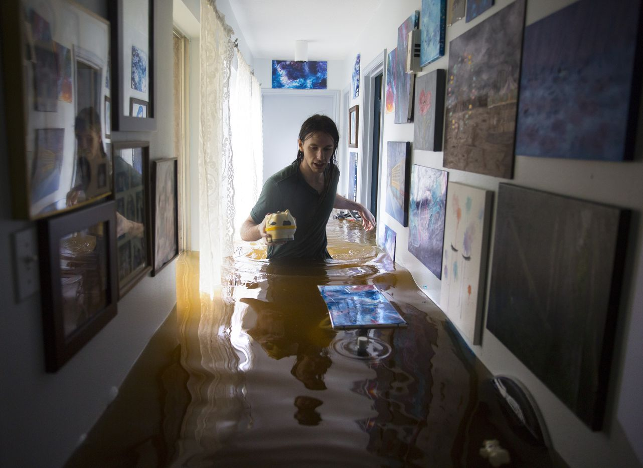 Matthew Koser looks for important papers and heirlooms inside his grandfather's house after it was flooded by heavy rains from Hurricane Harvey August 29, 2017 in the Bear Creek neighborhood of west Houston, Texas.