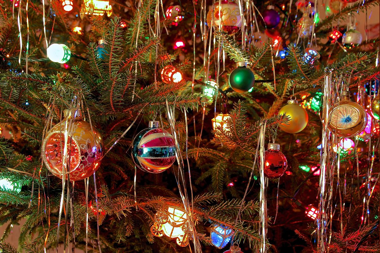 Close up of Christmas Tree decorated with antique glass baubles and colored lights in kitsch retro 70s style / iStock