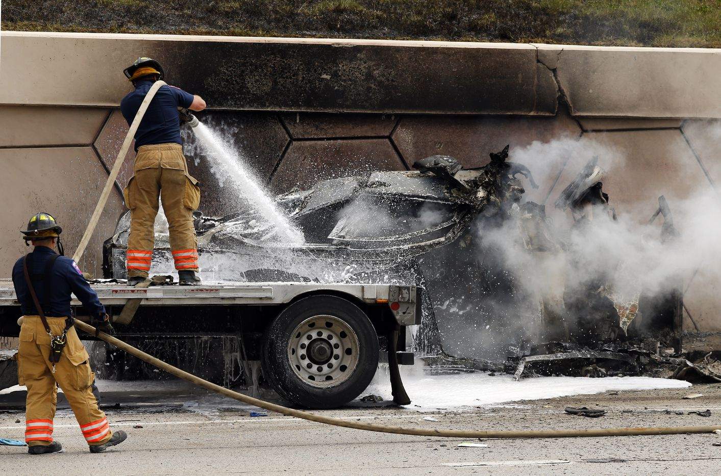 Arlington firefighters douse a burned out vehicle following a standoff with a man in a wrecked semi truck. The truck was involved in a high speed chase on Interstate 30 at Cooper St. in Arlington where it wrecked another vehicle causing the fire, Friday, June 9, 2017. The vehicle was between the truck and the wall of the interstate. (Tom Fox/The Dallas Morning News)