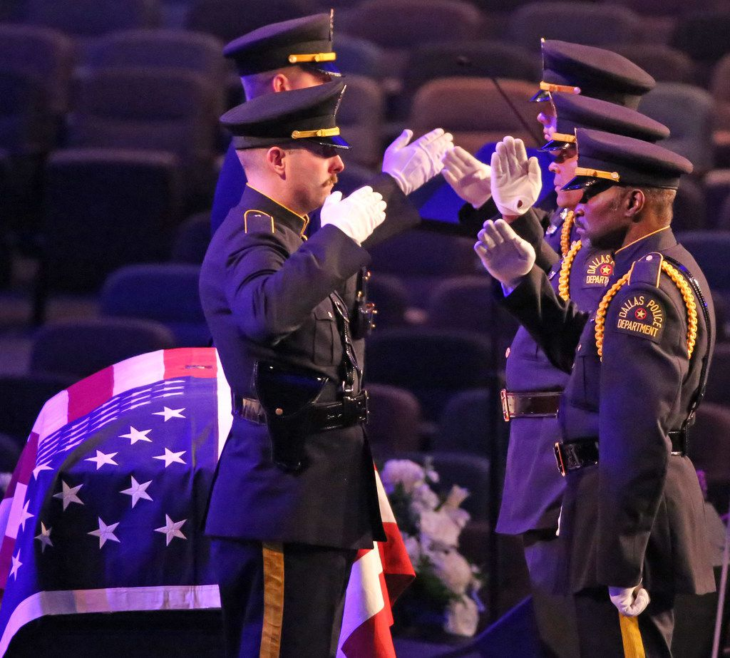 Members of the Dallas Police Honor Guard salute as they stand watch at the casket for Officer Rogelio Santander at Lake Pointe Church in Rockwall.