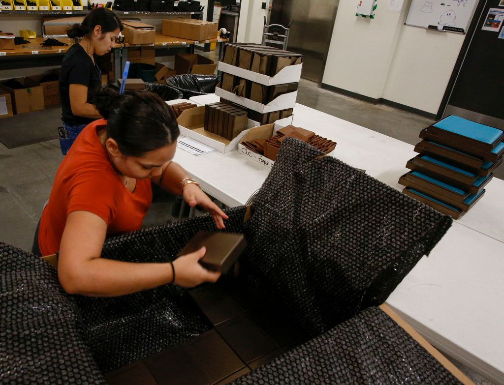 Zermira Alexander (front) and Yarima Maldonado pack up a corporate order at Leatherology.
