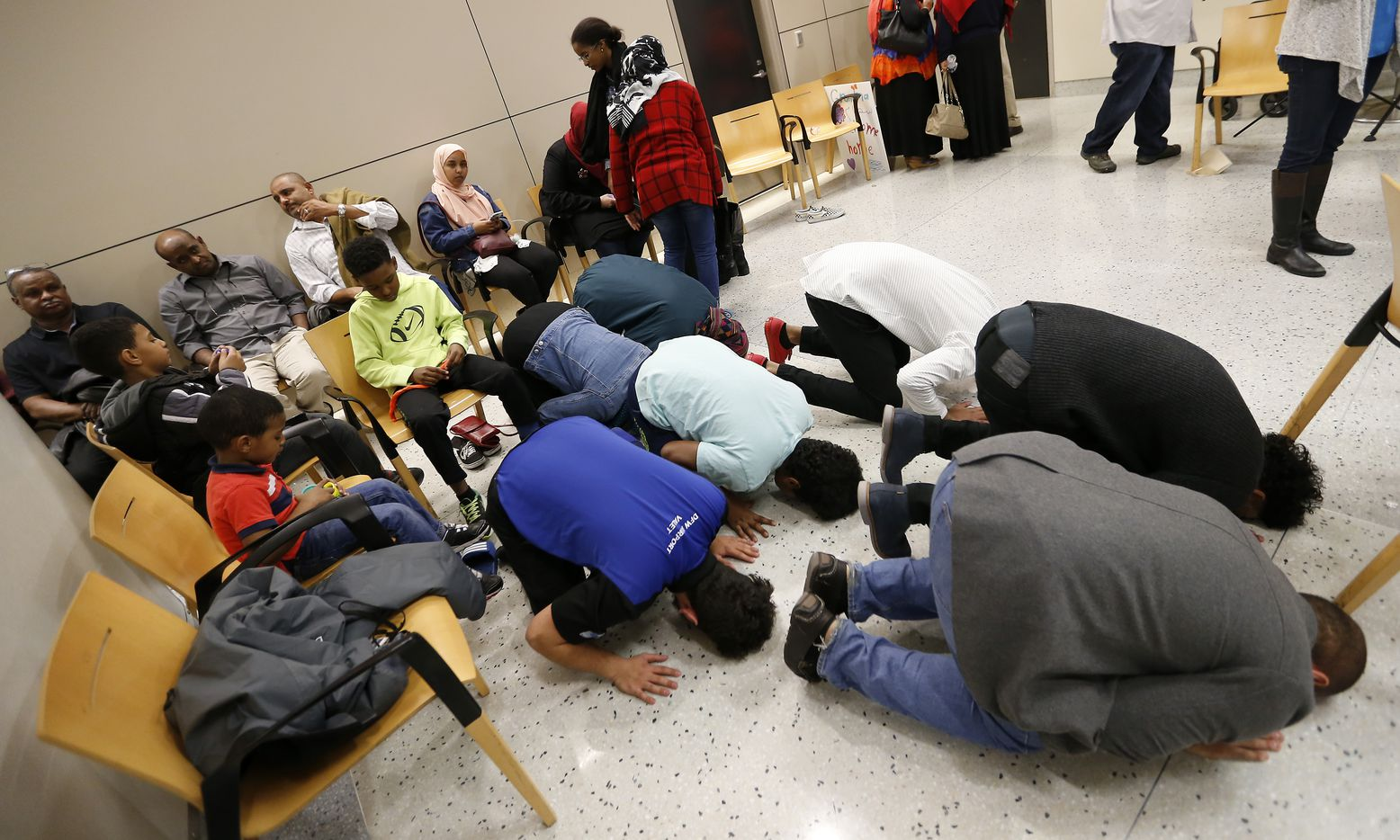 People pray at the international arrives at Dallas/Fort Worth International Airport in Dallas, Saturday, Jan. 28, 2017.