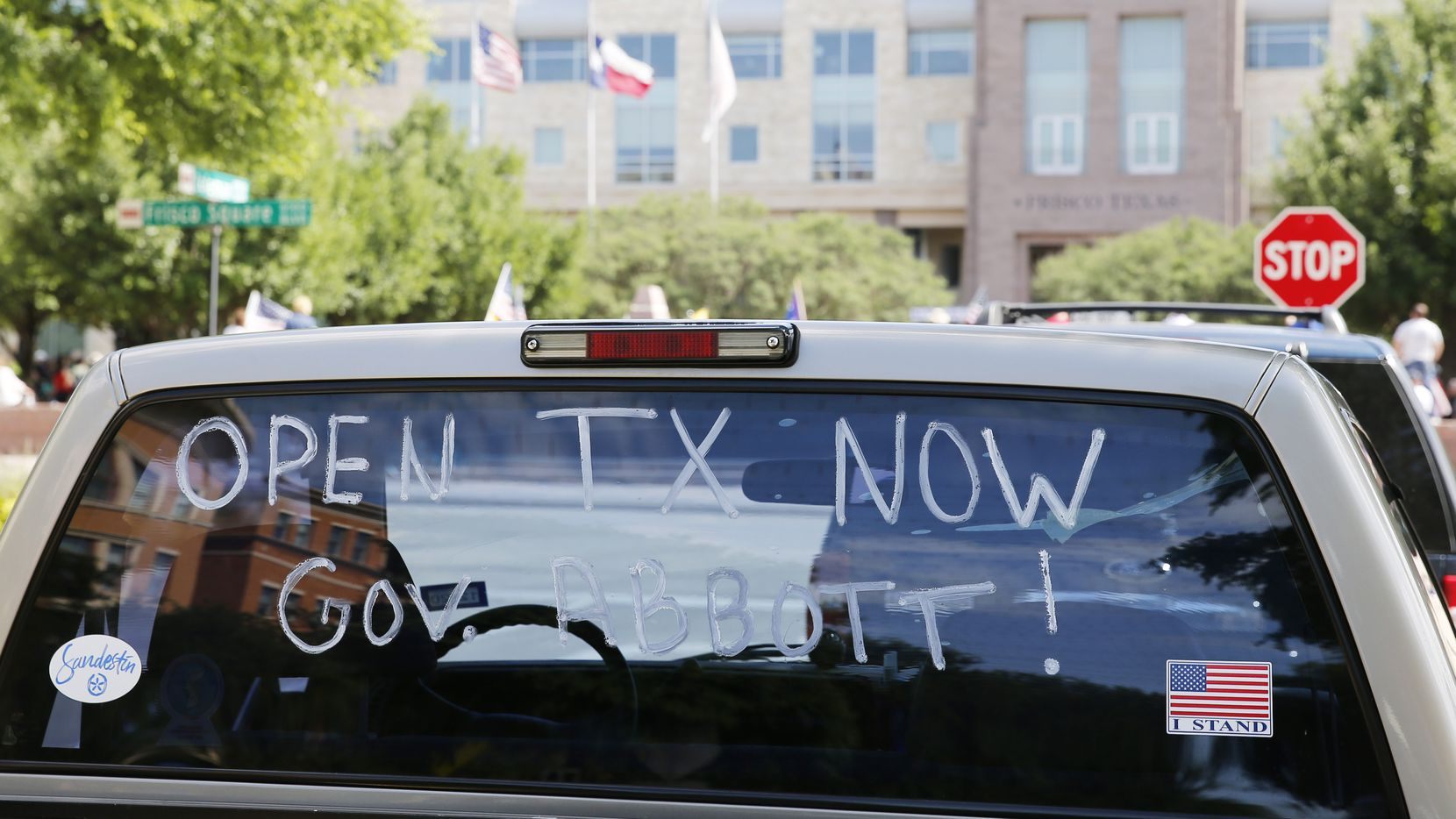 A message painted on a truck windshield promoted the reopening of Texas during a rally Saturday in front of the George A. Purefoy Municipal Center in Frisco.