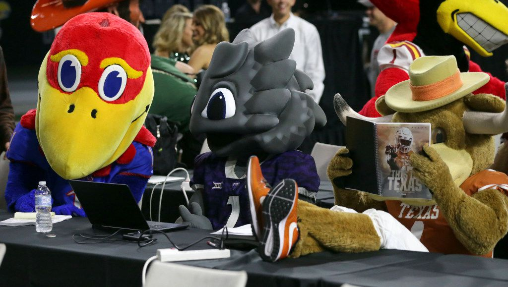 Team mascots for Kansas, TCU and Texas, from left, sit at desks for reporters before the start of news conference with head football coaches during the Big 12 NCAA college football media day in Frisco, Texas, Tuesday, July 18, 2017. (AP Photo/LM Otero)