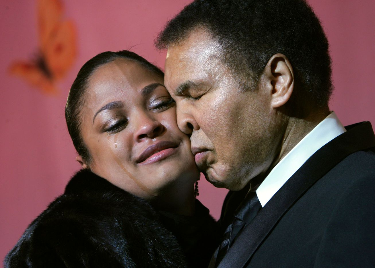 Laila Ali-McClain cries as she presses her cheek against her father, Muhammad Ali, as the two share the stage at the Butterfly Ball, a tribute to the elder Ali, coinciding with Black History Month, Saturday, Feb., 26, 2005, in Atlanta.