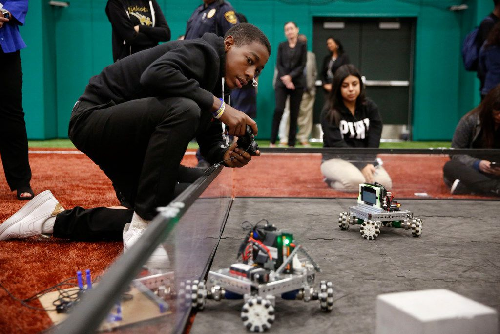 Jacari Westbrook, a freshman at L.G. Pinkston High School controls a robot during a grant announcement at the Texas Rangers MLB Youth Academy in Dallas on Friday, Sept. 7, 2018. Dallas ISD, Toyota and SMU will combine forces to open a school in West Dallas focused on science, technology, engineering and math instruction. (Rose Baca/The Dallas Morning News)