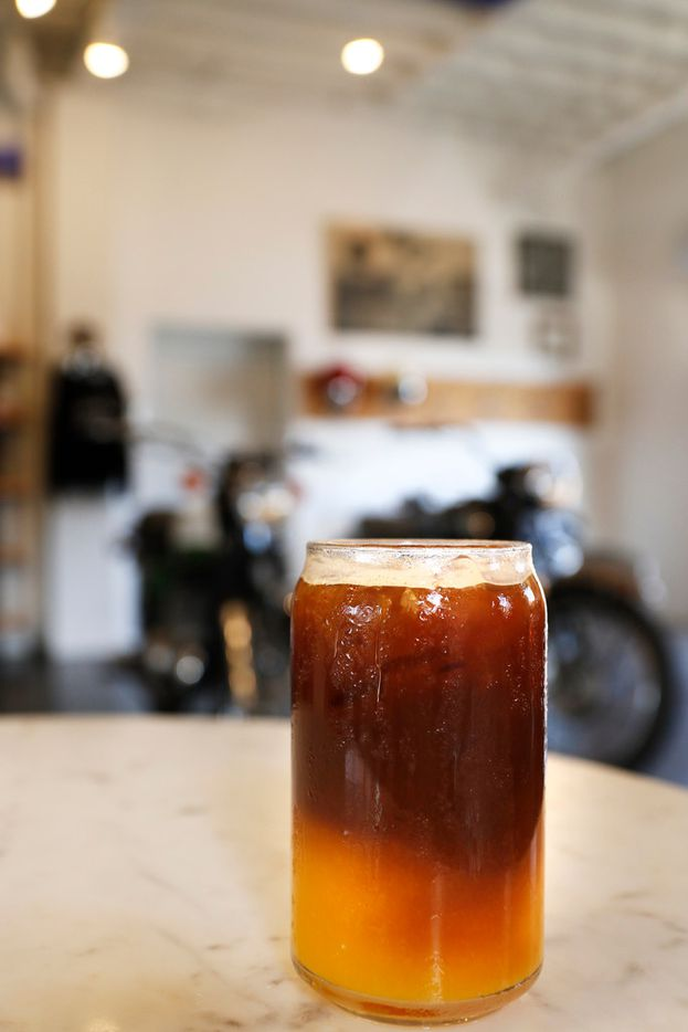 A glass of Sunrise Ice Coffee at Local Moto + Provisions, a vintage motorcycle repair shop that serves as an extension of Local Press in Dallas. They support local vendors while creating farm to bottle cold-pressed, organic juices served in glass bottles + classic coffee & espresso drinks. Photo taken on Monday, September 25, 2017. (David Woo/The Dallas Morning News)