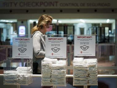 Bins of complimentary face masks are available to passengers passing through security screening at Dallas Love Field on Thursday, Jan. 7.