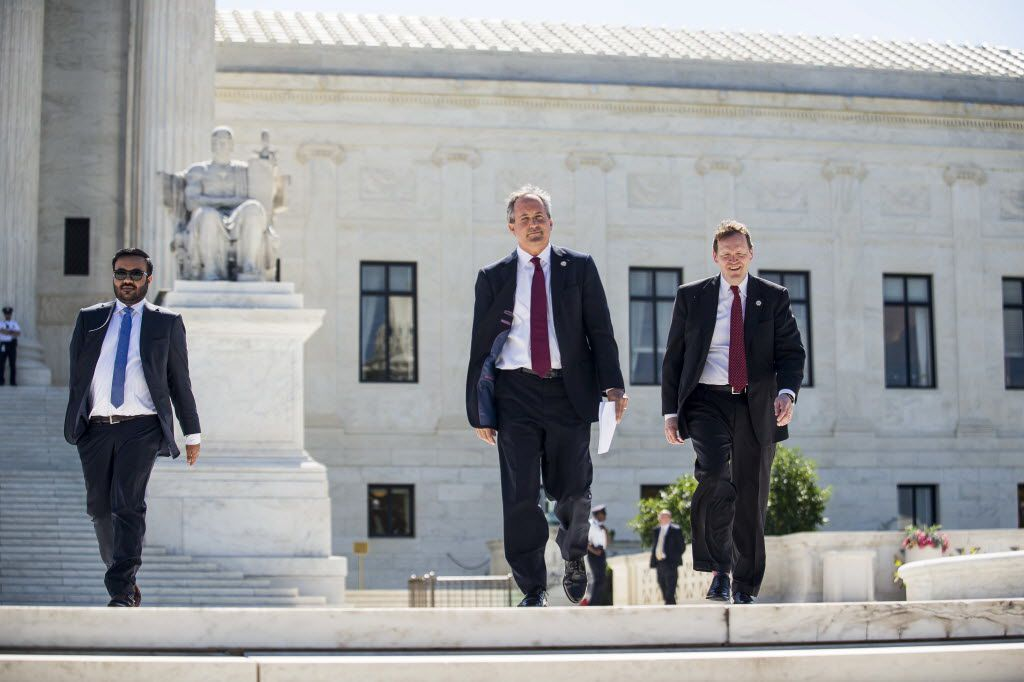 Texas Attorney General Ken Paxton (center)  walks to a news conference outside the Supreme Court on Capitol Hill on June 9, 2016, in Washington, D.C., when Paxton announced a lawsuit against the state of Delaware over unclaimed checks.