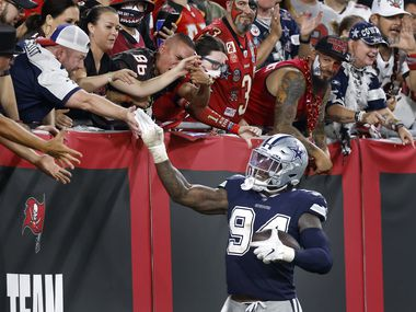 Dallas Cowboys defensive end Randy Gregory (94) receives high-fives from fans after his second quarter fumble recovery against the Tampa Bay Buccaneers at Raymond James Stadium in Tampa, Florida, Thursday, September 9, 2021. The Cowboys faced the Tampa Bay Buccaneers in the NFL season opener.