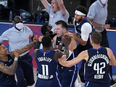 LAKE BUENA VISTA, FLORIDA - AUGUST 23: Luka Doncic #77 of the Dallas Mavericks celebrates with teammates after making a game-winning 3-point basket against the Los Angeles Clippers during overtime of Game Four of the first round of the playoffs between the Los Angeles Clippers and the Dallas Mavericks at the AdventHealth Arena at the ESPN Wide World Of Sports Complex on August 22, 2020 in Lake Buena Vista, Florida.