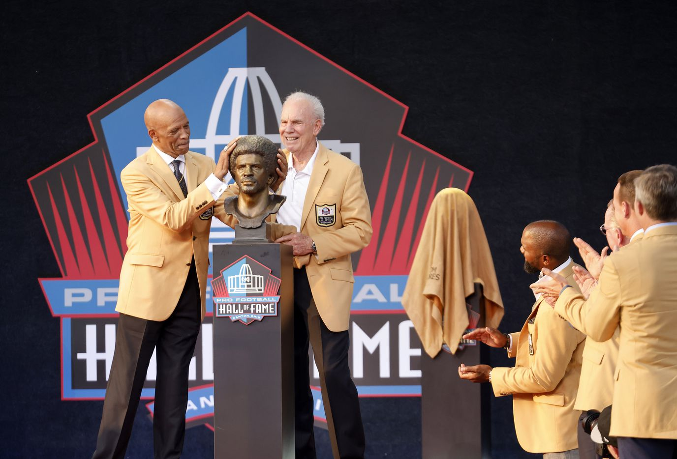 Pro Football Hall of Fame inductee Drew Pearson of the Dallas Cowboys (left) rubs his bronze afro after unveiling the bust with presenter and former Cowboy Roger Staubach during the Class of 2021 enshrinement ceremony at Tom Benson Hall of Fame Stadium in Canton, Ohio, Sunday, August 8, 2021. (Tom Fox/The Dallas Morning News)