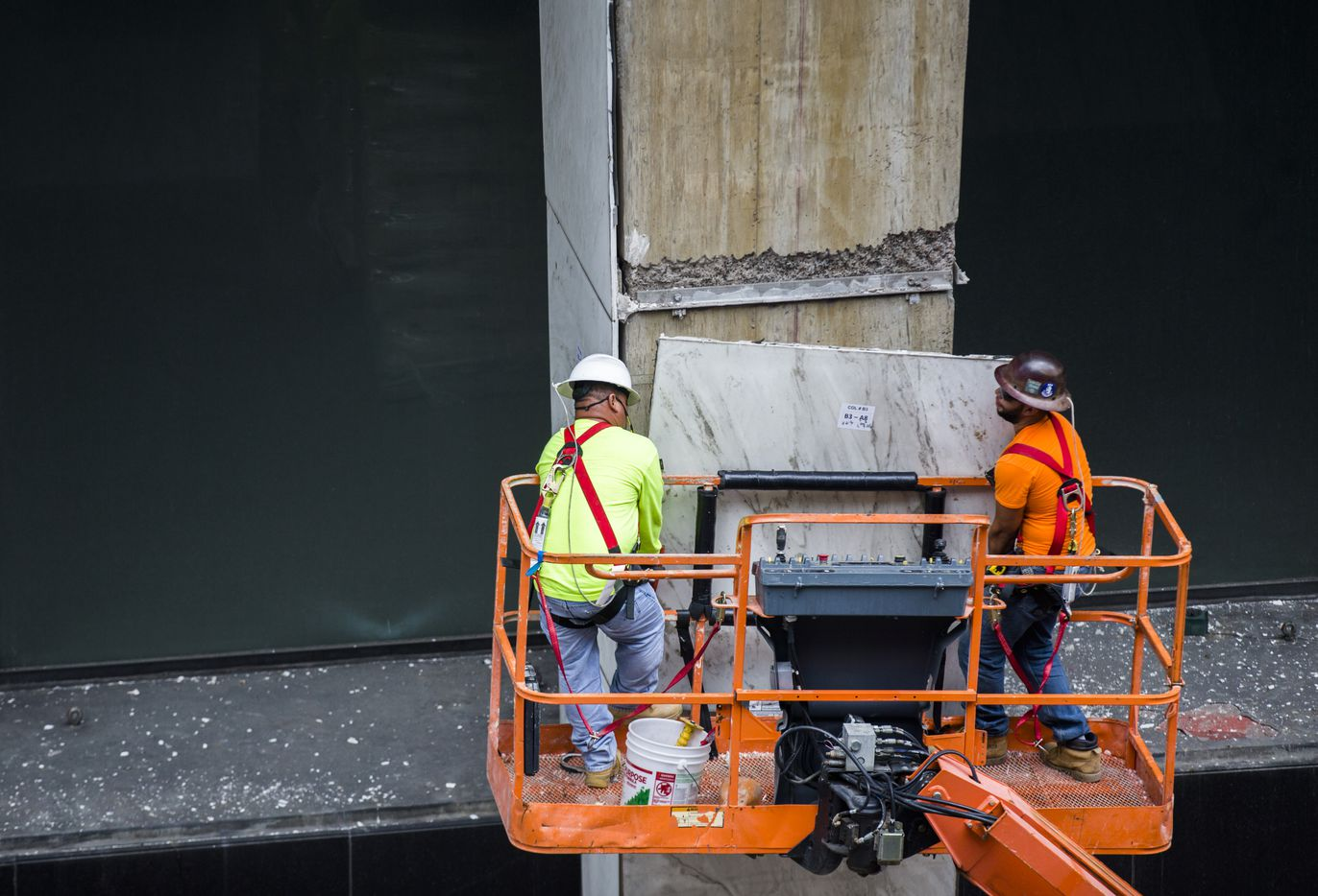 Workers remove panels of marble off of the First National Bank Tower as part of the renovation of the skyscraper.