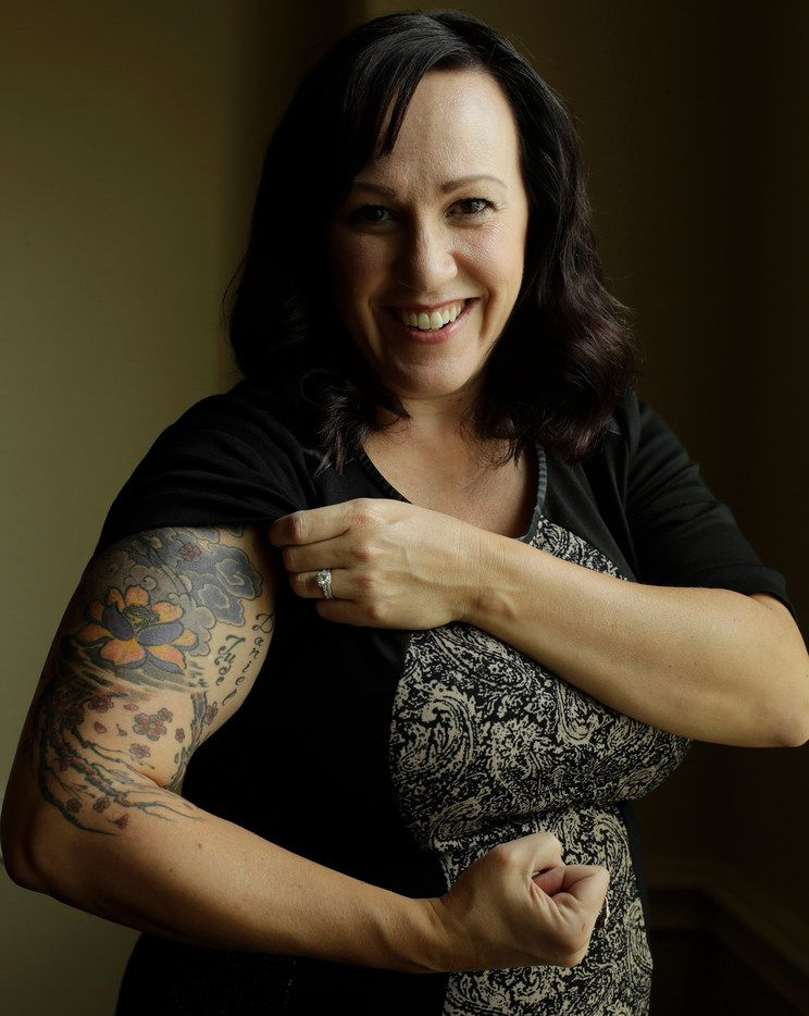 MJ Hegar pulls up her sleeve to reveal part of a tattoo that winds around her arm and back, for a portrait at her home in Round Rock, Texas,, on Aug. 9, 2018. Nine years after being shot down in Afghanistan, winning a lawsuit against the federal government, and writing a book, Hegar is running for Congress against Rep. John Carter, R-Round Rock.