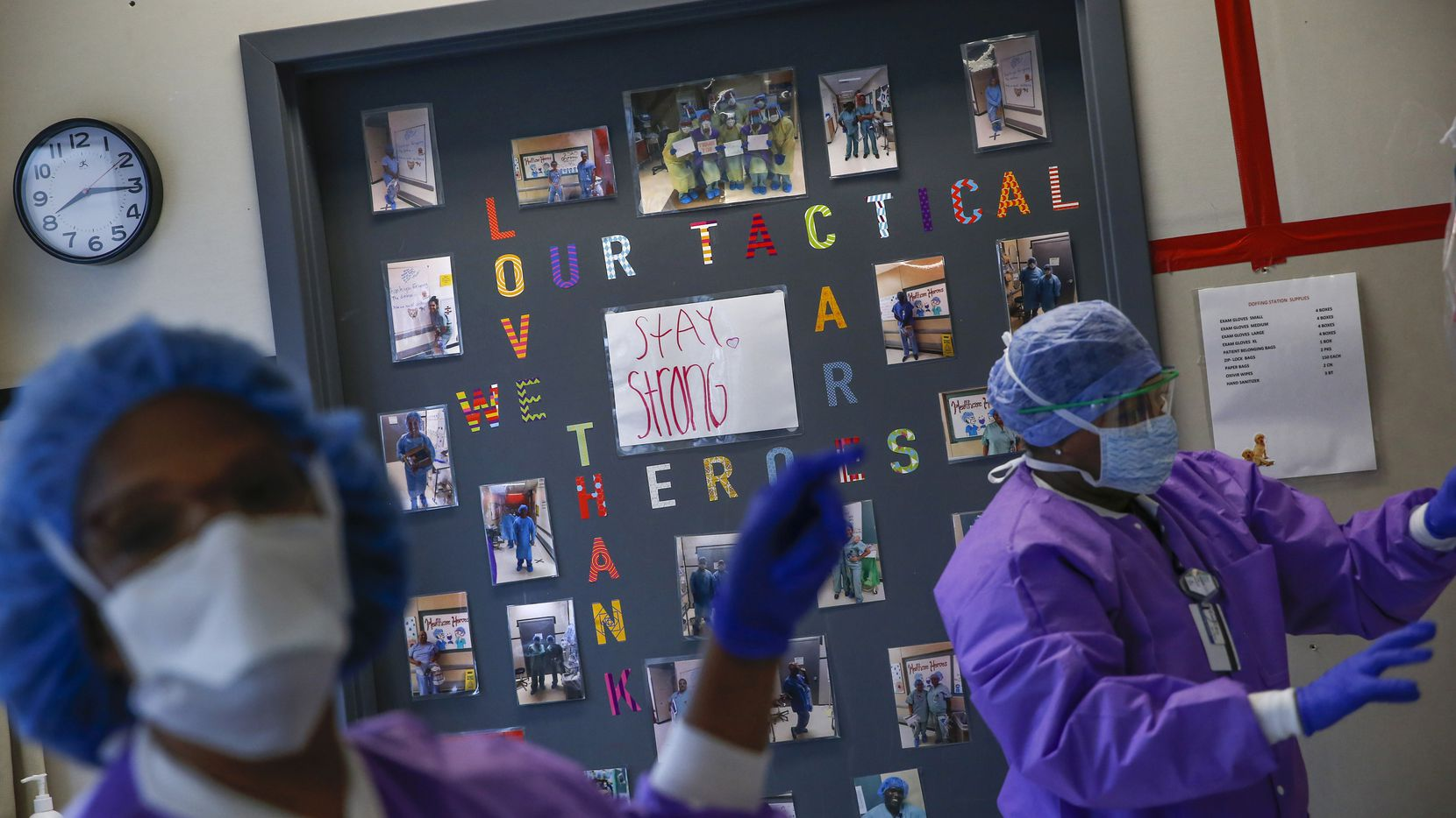 """Health care workers Deborah McElroy, left, and Gina Ousley clean face shields in the COVID-19 Tactical Care Unit at Parkland Memorial Hospital on Wednesday.  """"We're wiping them all off to make sure they're clean to see through for the workers to head back in,"""" Ousley said."""