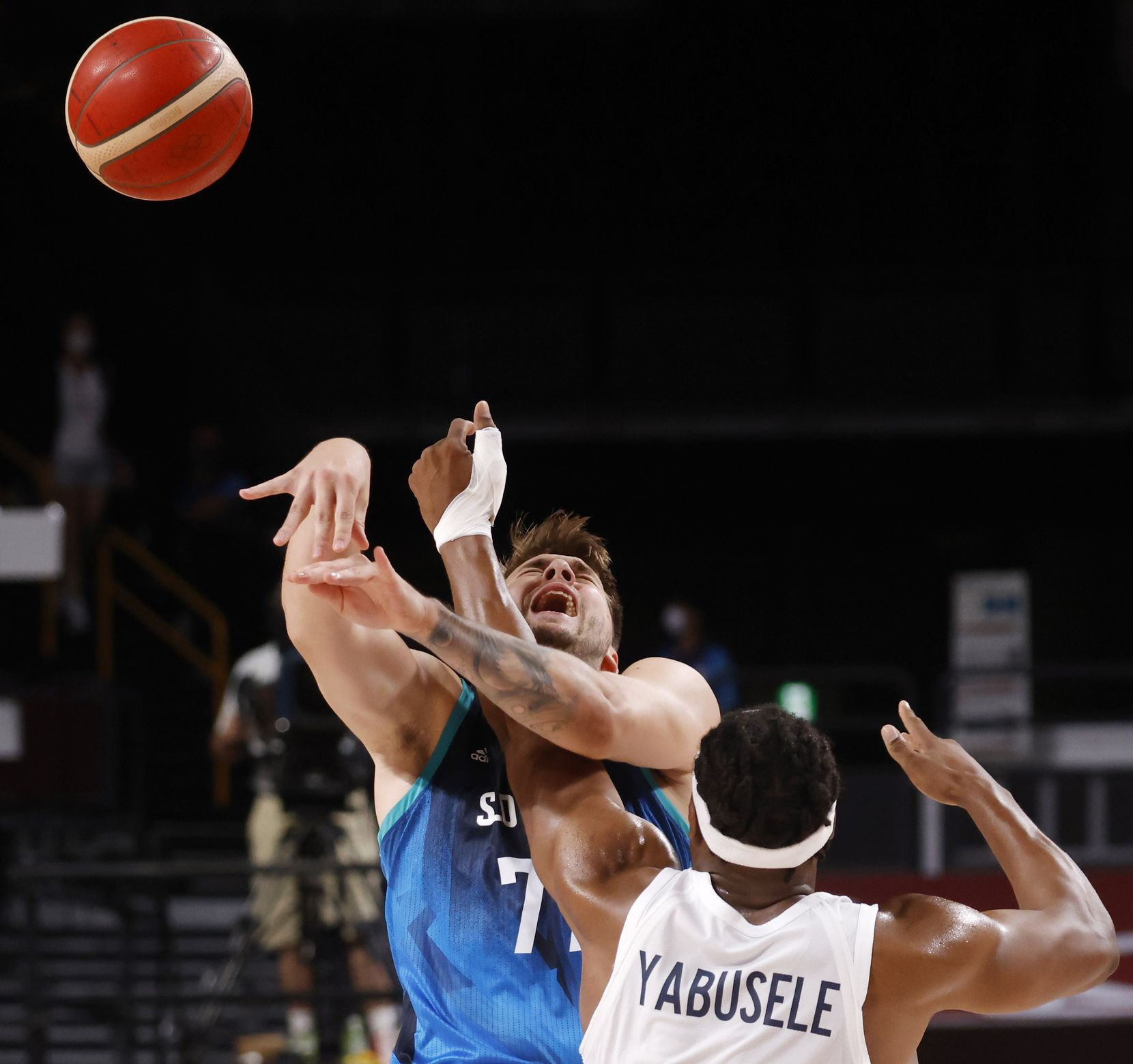 Slovenia's Luka Doncic (77) passes the ball as he is hit by France's Guerschon Yabusele (7) during the first half of a men's basketball semifinal at the postponed 2020 Tokyo Olympics at Saitama Super Arena, on Thursday, August 5, 2021, in Saitama, Japan. (Vernon Bryant/The Dallas Morning News)