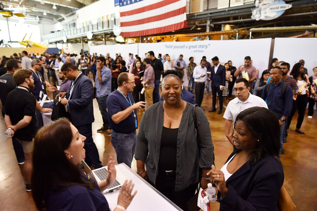 Lizzie Myers, left, an Amazon sales recruiter, speaks with Marie Wilson, 38, right, and Crystal Taylor, 38, far-right, both of Dallas, during the Amazon job fair in Dallas. The women were looking for a job in sales or human resources.