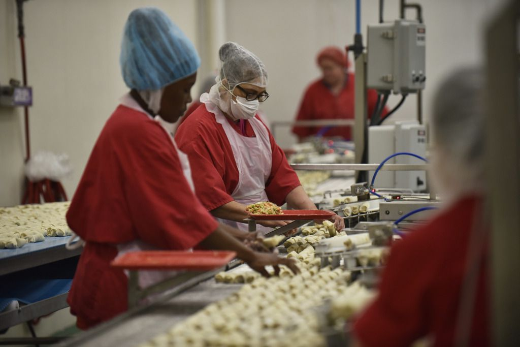Employees inspect egg rolls as they move on conveyor belts for frying at the Van's Kitchen production plant.
