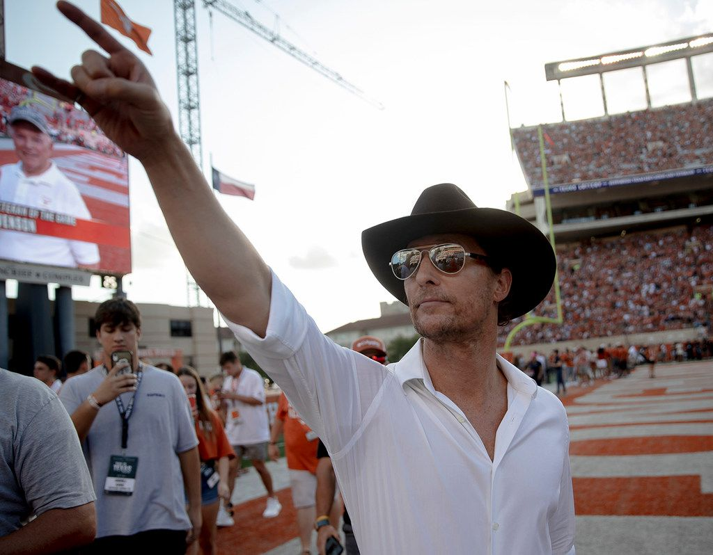 "Actor Matthew McConaughey holds up the ""Hook 'Em Horns"" sign to Texas fans before a game against Oklahoma State in 2019, at Royal Texas Memorial Stadium in Austin, Texas."