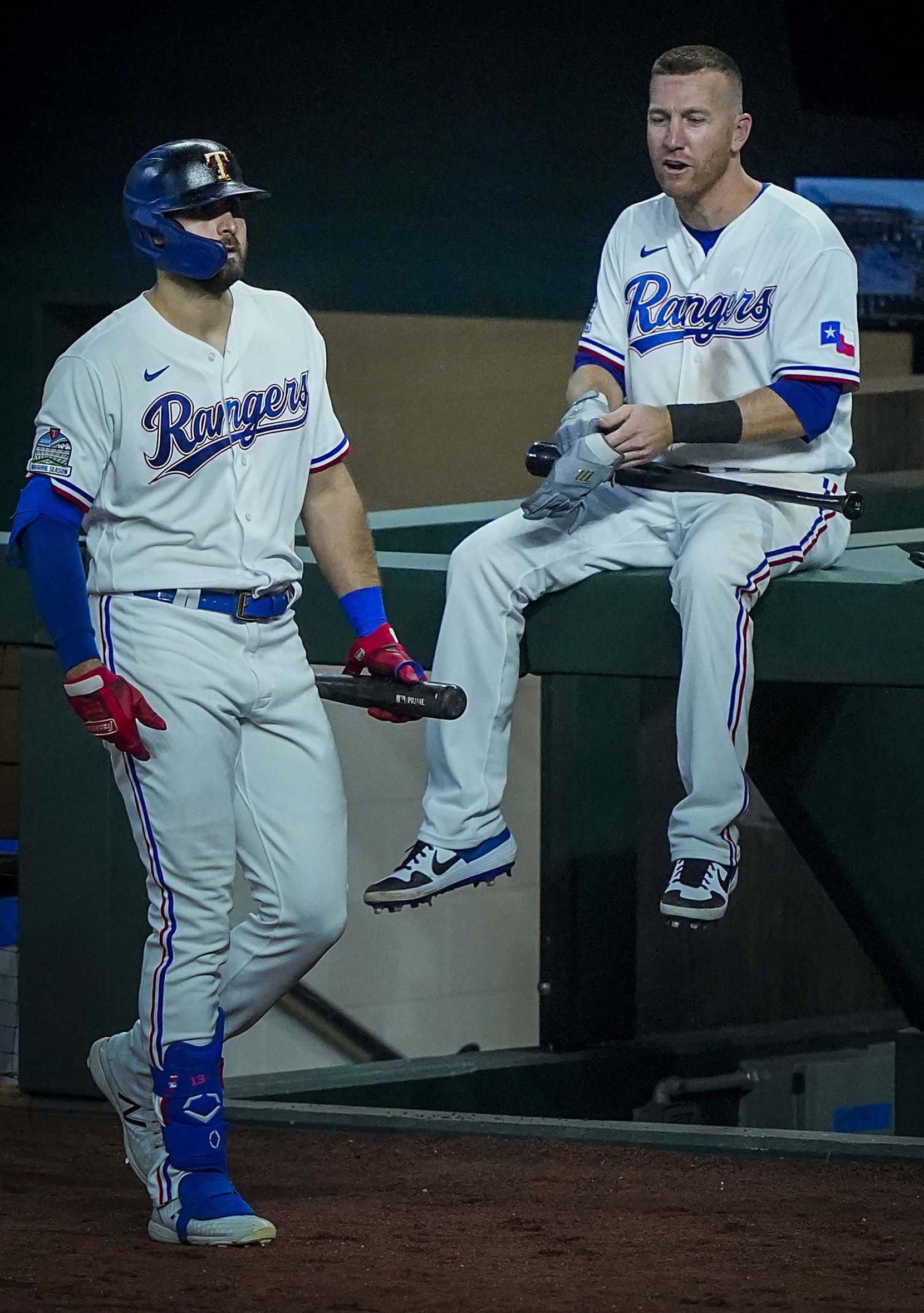 Outfielder Joey Gallo passes third baseman Todd Frazier perched atop the dugout rail as he heads to the plate during Texas Rangers Summer Camp at Globe Life Field on Thursday, July 16, 2020.