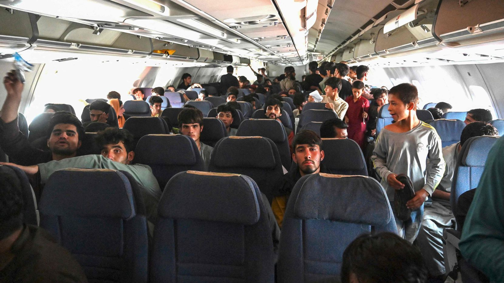 Afghan passengers sit inside a plane as they wait to leave the Kabul airport in Kabul on Aug. 16, 2021, after a stunningly swift end to Afghanistan's 20-year war, as thousands of people mobbed the city's airport trying to flee the group's feared hard-line brand of Islamist rule.