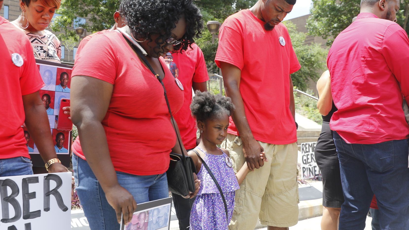 Jordan Edwards' stepmother, Charmaine Edwards, sister Korrie Edwards, and father, Odell Edwards, bowed in prayer at the Frank Crowley Courts Building on May 13, 2017, during a rally remembering Jordan and others killed by police.