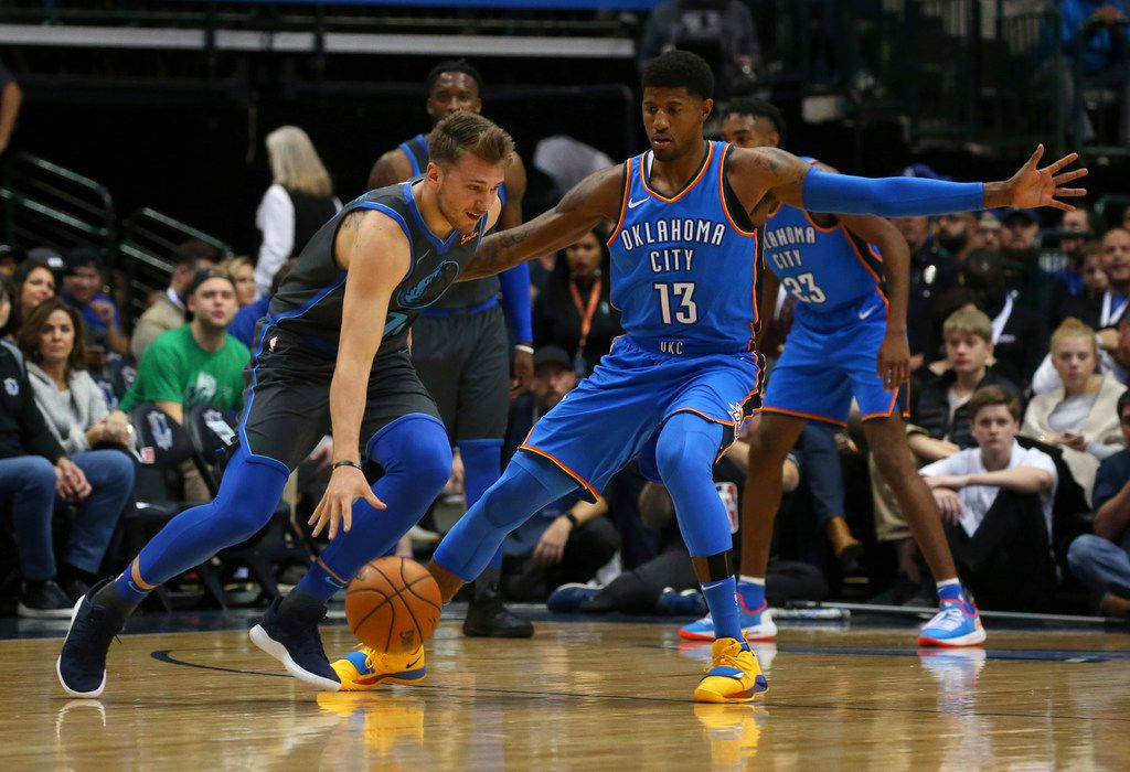 Dallas Mavericks forward Luka Doncic (77) tries to drive past Oklahoma City Thunder forward Paul George (13) in the first quarter of an NBA basketball game Saturday, Nov. 10, 2018, in Dallas. (AP Photo/Richard W. Rodriguez)