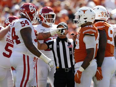 Oklahoma Sooners offensive lineman Marquis Hayes (54) and Texas Longhorns defensive lineman Ta'Quon Graham (49) are split apart by an official during the second half of play in the Red River Showdown at the Cotton Bowl in Dallas on Saturday, October 12, 2019. Oklahoma Sooners defeated Texas Longhorns 34-27. (Vernon Bryant/The Dallas Morning News)