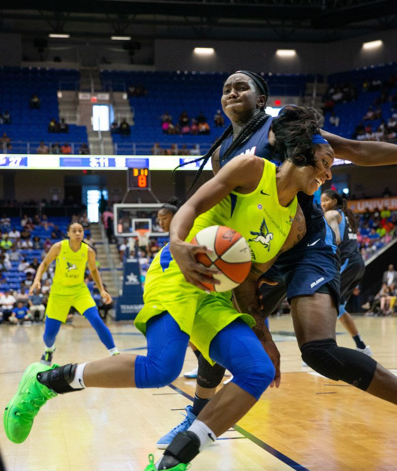 Dallas Wings forward Glory Johnson (center) drives the ball past Atlanta Dream center-forward Elizabeth Williams during the second quarter of a WNBA game between the Dallas Wings and the Atlanta Dream on Saturday, June 15, 2019 at College Park Center on the UTA campus in Arlington.  (Lynda M. Gonzalez/The Dallas Morning News)