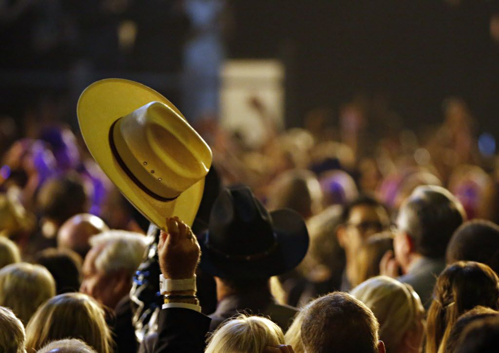 A fan waves his hat in the air during the 2015 Academy of Country Music Awards Sunday, April 19, 2015 at AT&T Stadium in Arlington, Texas.
