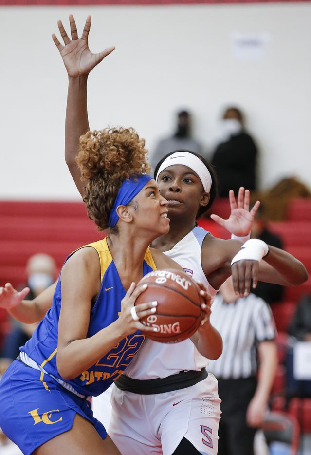 Lakeview Centennial senior Sanna Baker (22) attempts a shot as Skyline sophomore Jaida McDonald (13) defends during a girls basketball first-round playoff game at Hillcrest High School in Dallas, Saturday, February 13, 2021. (Brandon Wade/Special Contributor)