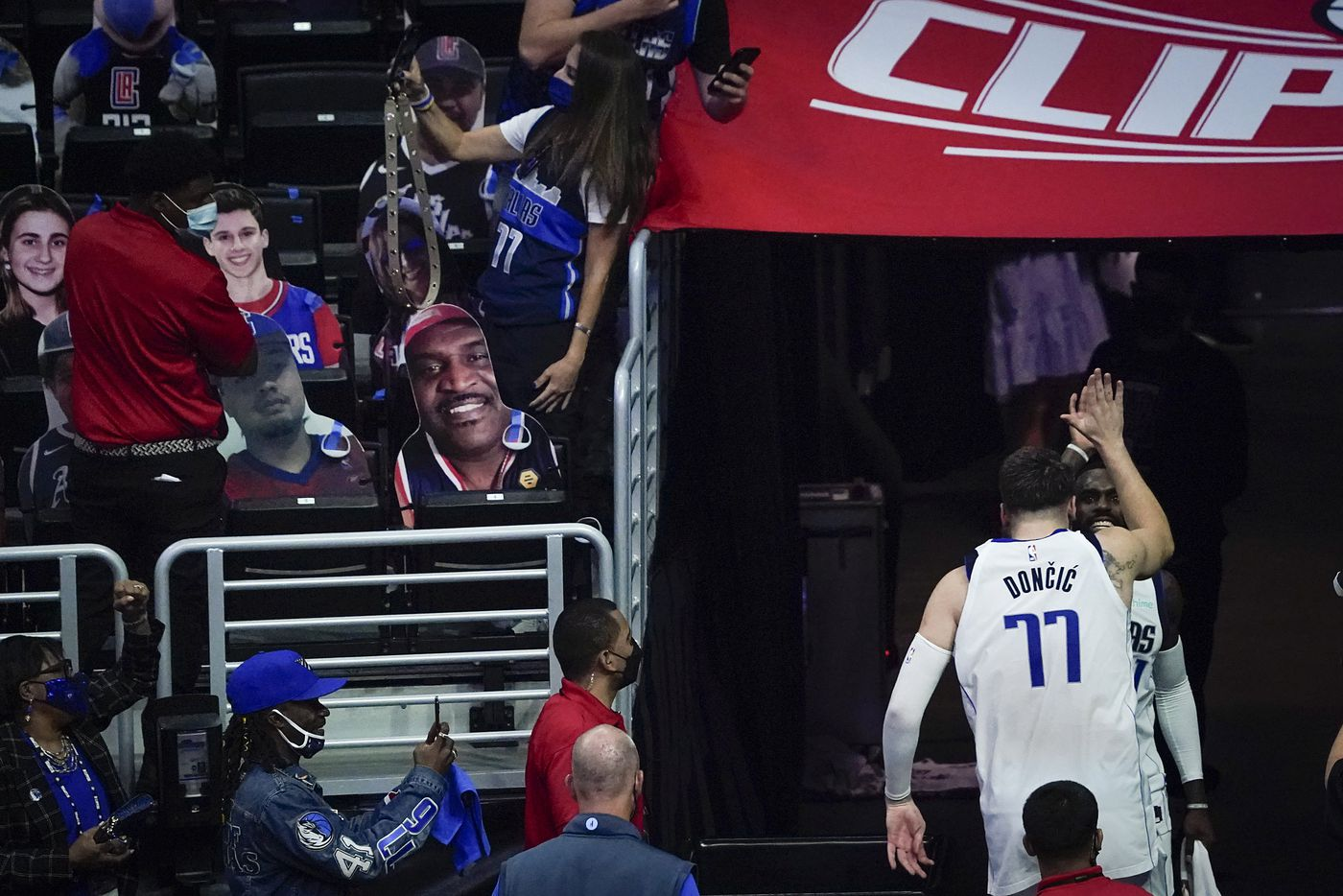 Dallas Mavericks guard Luka Doncic (77) celebrates with forward Tim Hardaway Jr. (11) as they leave the court after the Mavericks 127-121 victory over the LA Clippers in an NBA playoff basketball game at Staples Center on Wednesday, May 26, 2021, in Los Angeles.